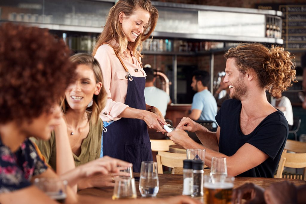 happy customers paying at a restaurant
